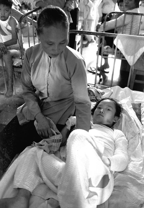 Two days after the attack, Kim Phuc is comforted by her mother in a Saigon hospital. Image source ABC News. (Robinson/AP Photo)